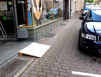 Gehweg auf der linken Straßenseite. Links des Gehweges zu sehen ist eine kleine Rollstuhlrampe die zu einem ca 10 cm erhöhten Eingang führt. Auf der rechten Seite des Gehweges ist ein Auto geparkt und lässt wenig Platz zur Rollstuhlrampe.