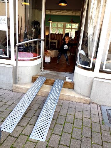 Zwei metallene ca 2 m lange Schienen für Rollstuhlfahrer führen über zwei Stufen in einen Laden. Ein kleiner Junge steht im Laden und schaut heraus auf den Betrachter.