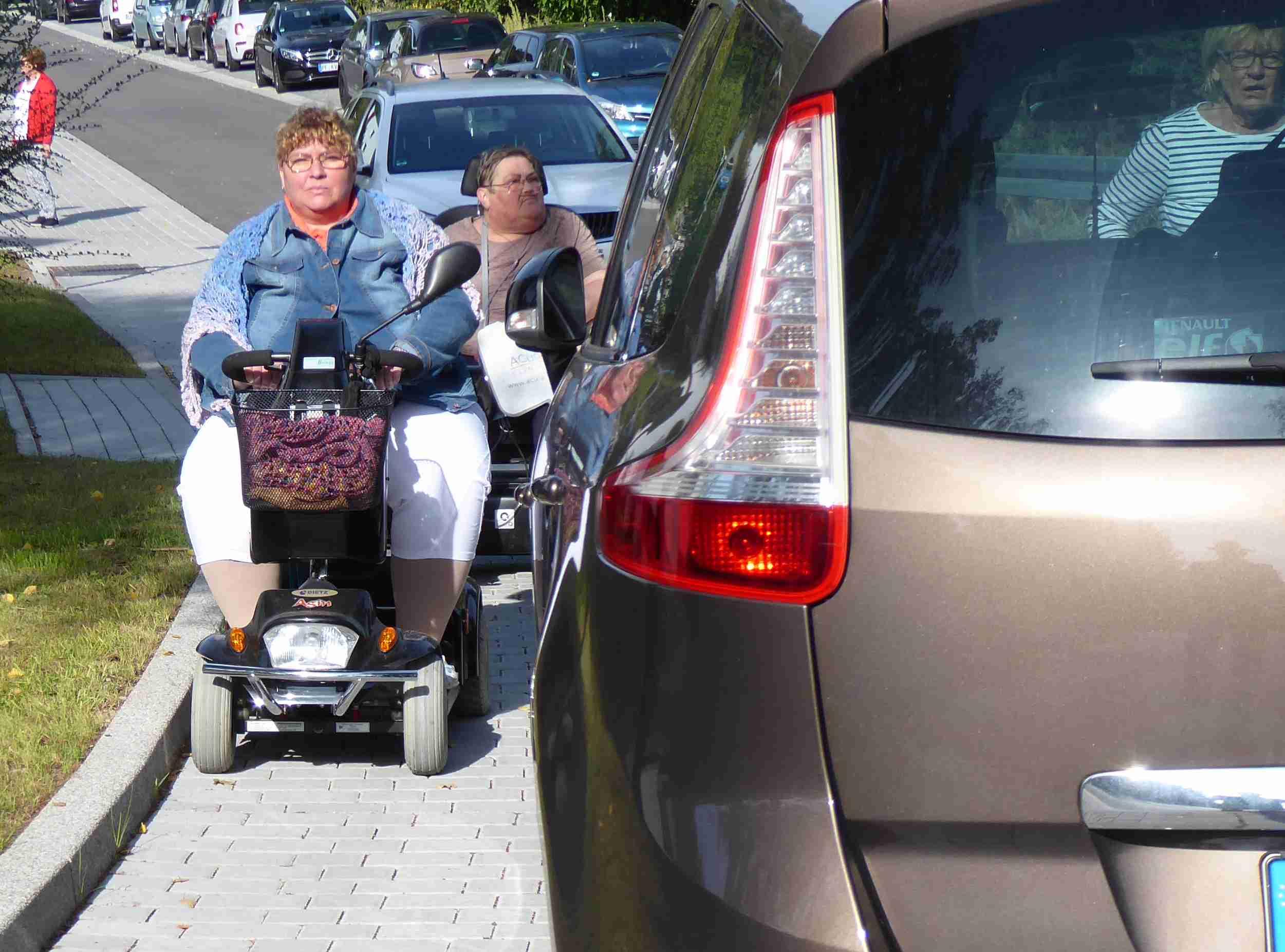 Einer Rollstuhlfahrerin ist es fast unmöglich auf dem Bürgersteig zwischen Kante und geparktem Auto durchzufahren.