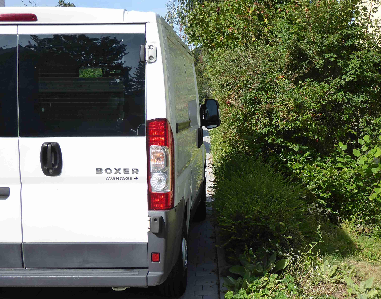 Ein auf dem Gehweg parkender Transporter lässt nur wenige cm zur Hecke frei.