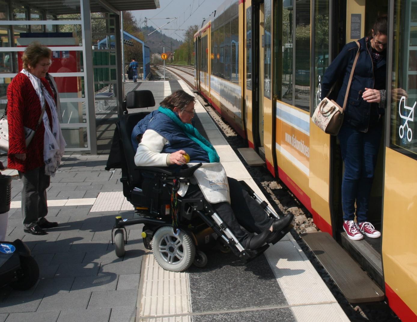 Frau Petra Schultern im E-Rolli fährt vom Ispringer Bahnhofsgleis Richtung Pforzheim in eine gelbe AVG Bahn ein. Die Türen der Straßenbahn werden durch Lena Kautz offengehalten indem sie die Lichtschranke versperrt. Frau Illona Geisselhardt beobachtet vom Bahngleis aus wenigen Metern Entfernung das Geschehen.
